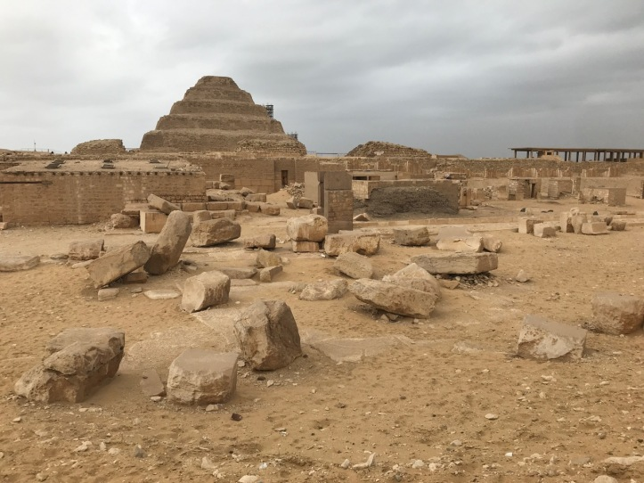 A sandy field covered in rocks with the Step Pyramid in the background
