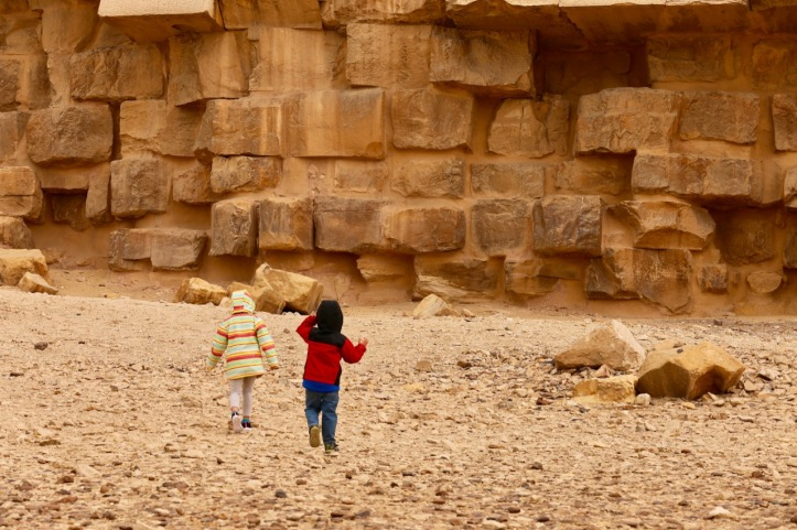 Two kids run towards the side of a pyramid