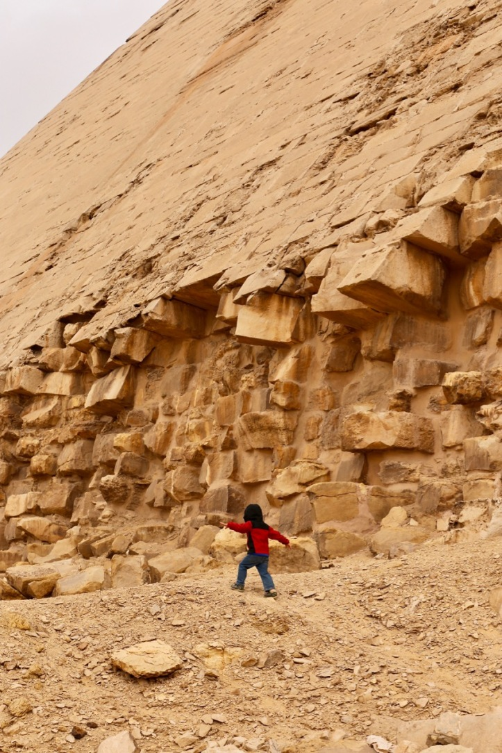 A small boy in a red and black coat runs up a hill near a pyramid