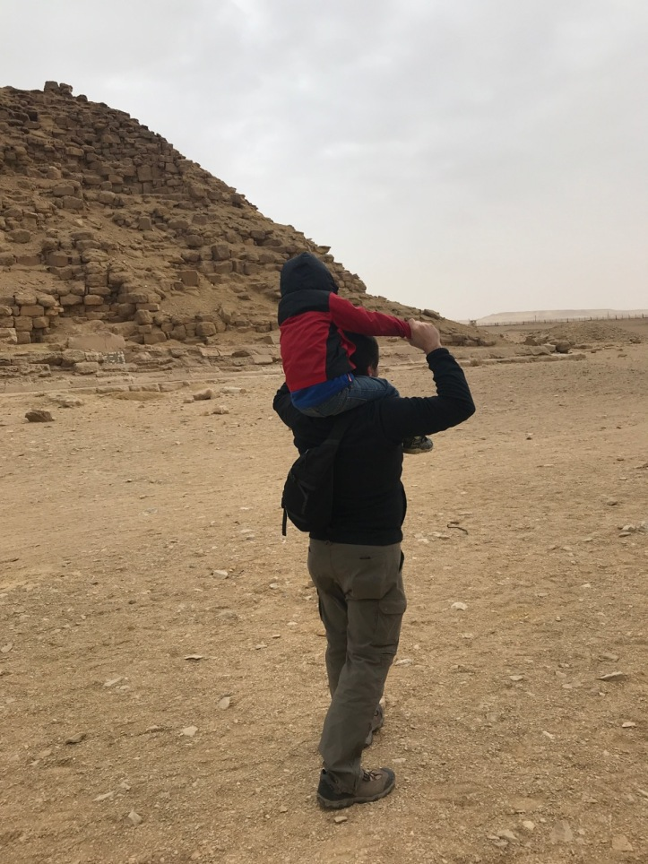 A young boy gets a ride on his dad's shoulders at a pyramid